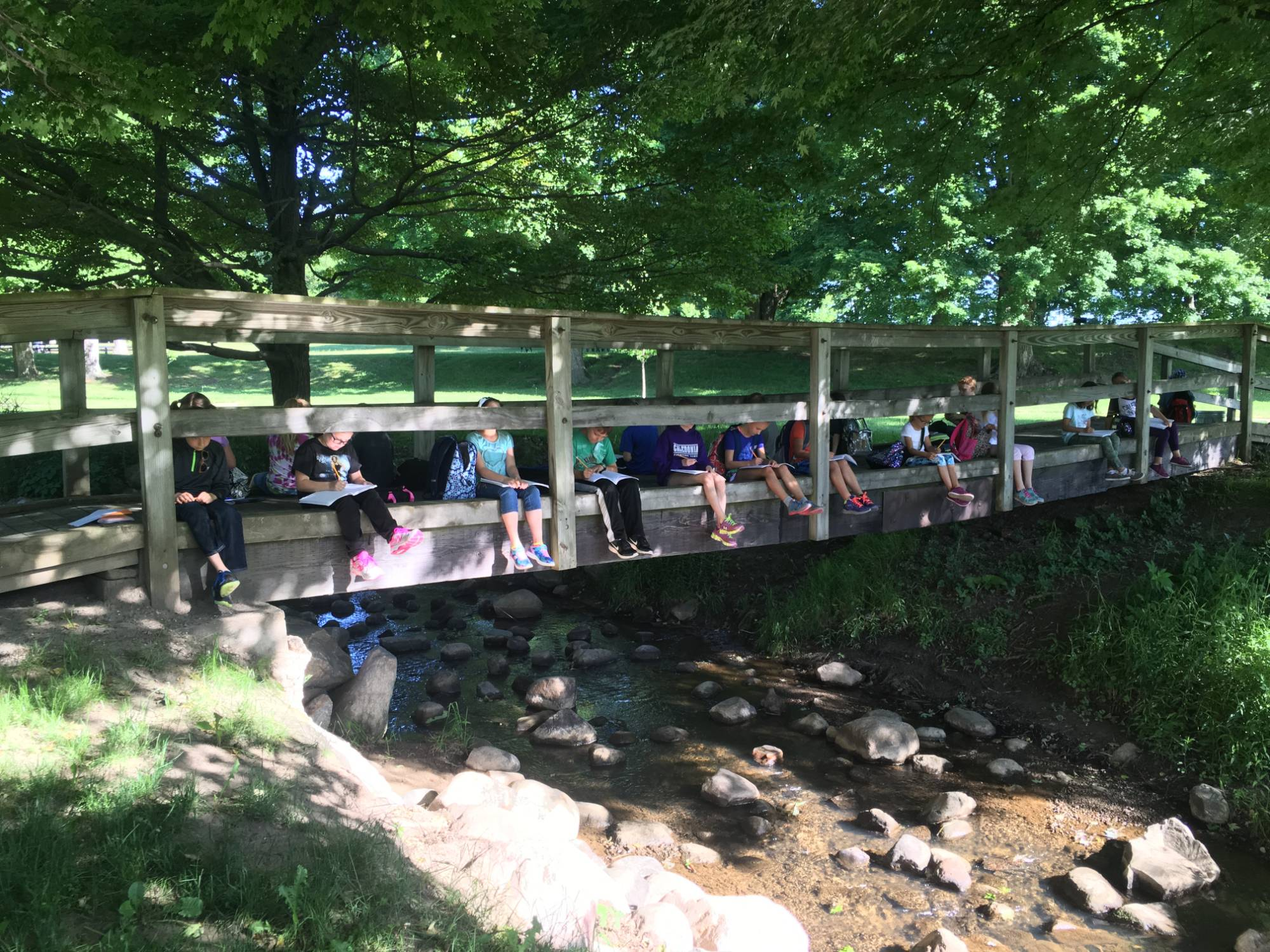 Students sit on bridge above stream